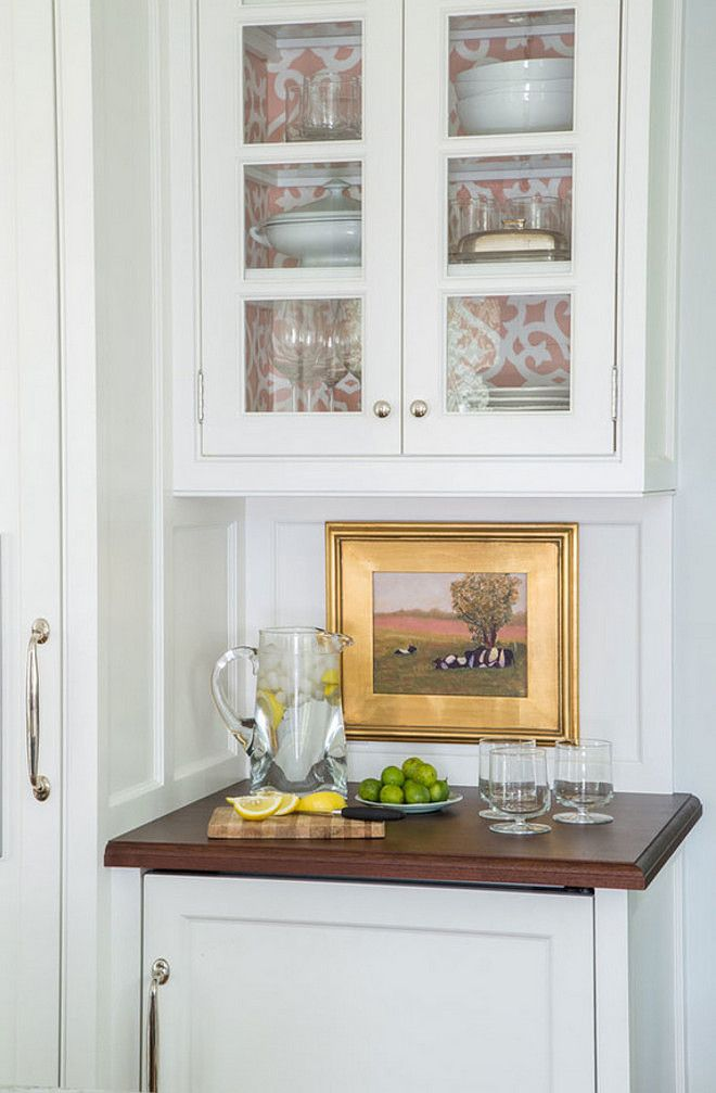 small oil painting decorates the backsplash of the corner bar cabinet next to the fridge taste design inc