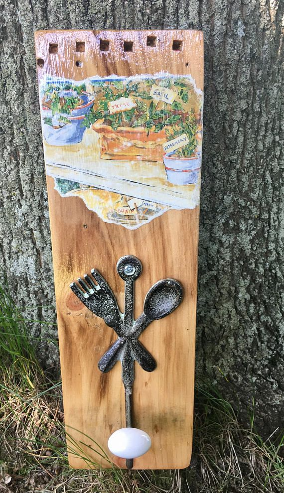 Raw rustic spoon and fork wall hook hanging with herb garden