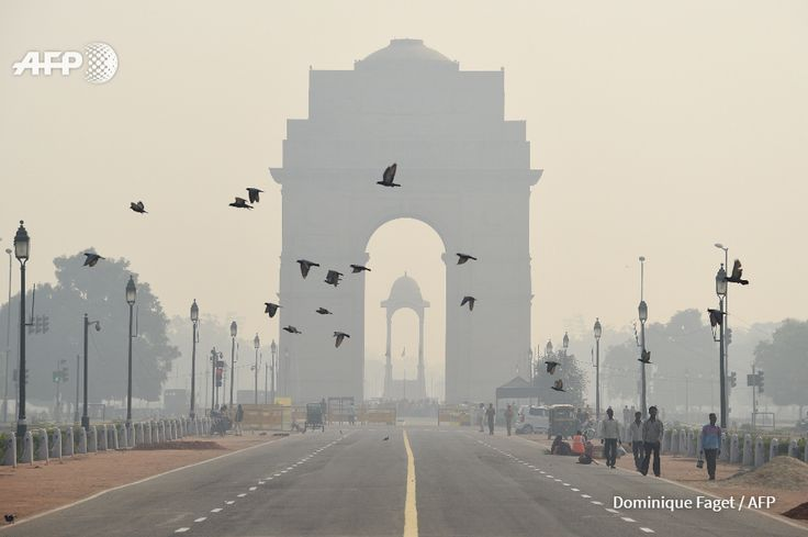 Indian pedestrians walk near the India Gate monument amid heavy smog in New Delhi on October 28, 2016. India's capital, with 18 million residents, has the world's most polluted air, worsening in winter as temperatures drop and farmers burn off fields...
