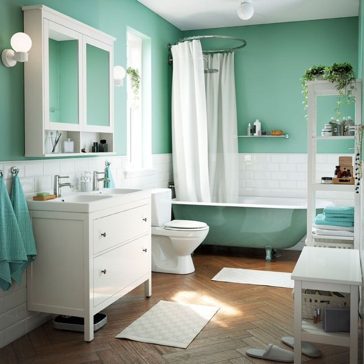 A light green, blue and white bathroom with traditional bathtub and double sink cabinet.