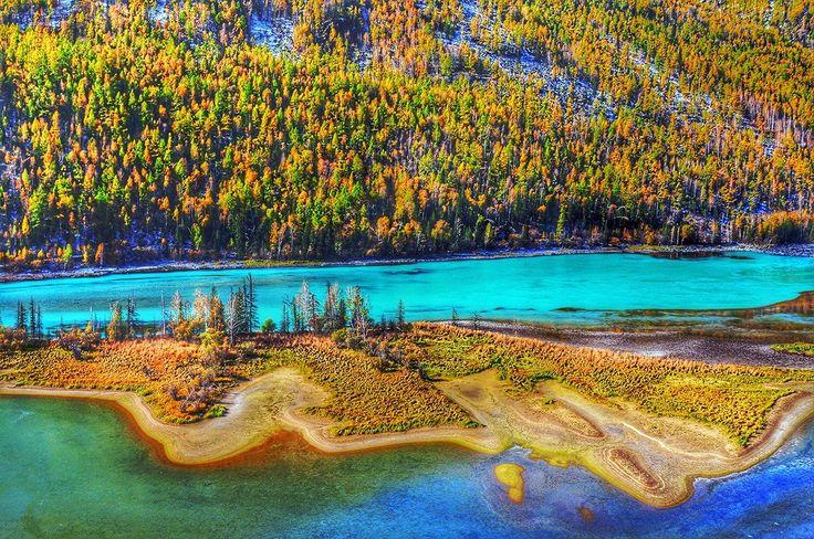 中国の最西端に位置する新疆ウイグル自治区。豊かな民族風情と独特な自然環境に恵まれ、多くの観光資源を有しています。カナス自然保護区は最も特徴のある景観に恵まれています。カナス湖は新疆北部アルタイ山の中部森林地帯にある美しく神秘に包まれた天然湖。およそ20万年前フィヨルドによって形成され、海抜は1374m、面積37.7km2。周囲を取り囲んで重なり合う山並みの風景はとても美しいものです。「カナス」はモンゴル語で「神秘的で美しい」という意味を持ち、その名に違わず神秘的で美しく、湖は季節や天候によって湖面の色が変わることで変色湖の異名を持ちます。氷河に含まれる鉱物により、澄んだ紺碧、晴れた日はエメラルドグリーン、曇った日は灰緑色、暑い日には乳白色などとさまざまに色を変化させます。地元の人たちは「四季すべてが美しい。春には花が咲き乱れ、夏には湖上の波が立ち、秋には木々が色づいて、冬には銀の衣装をまとう。」とこの地を讃えています。
