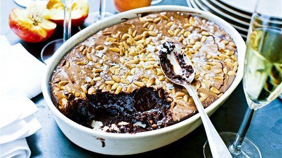 Sätt ugnen på 175°. Smörj en form med olja (ca 26 cm i diameter). Rör ägg och socker försiktigt, det ska inte bli pösigt. Vispa in oljan. Smält chokladen över vattenbad. Blanda in choklad, vetemjöl och 1 krm salt i smeten. Häll i smeten och toppa med pinjekärnor och flingsalt. Baka i mitten av ugnen ca 20–25 minuter. Kolla med en sticka att kakan är klar, den ska vara kladdig men inte rinnig!