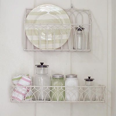 """Store with style. Wall-mounted metal racks provide stylish storage spaces inside the cozy cottage. Look for similar vintage country """"spice""""                                            racks at local flea markets or antiques shops"""