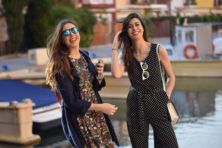 Claudia Peris wearing polka-dot jumpsuit with masculine loafers, white sunglasses, and black leather jacket. Lucía Peris is wearing floral midi dress, navy-blue trench, white sneakers, coral mini backpack, and blue sunglasses (midilema.com)