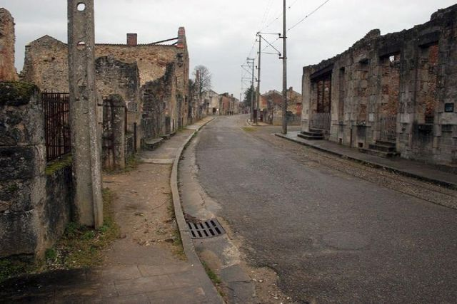 Abandoned town- Oradour-Sur-Glane.This town was abandoned because the Nazis rounded all the citizens up and killed them. France left the entire town untouched as a memorial. The people were buried, but the items; cars, bikes, baby carriages, still remain.