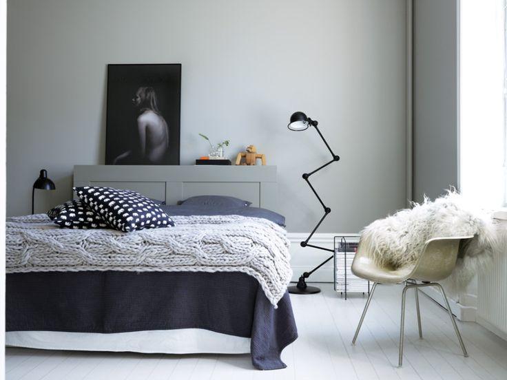 Ett sovrum i gråskala. Blanda olika gråa nyanser för att skapa ett balanserat och fridfullt sovrum. Väggen är målad med kulören Gåsdun 503 och Sänggaveln i Lovikagrå 505.
