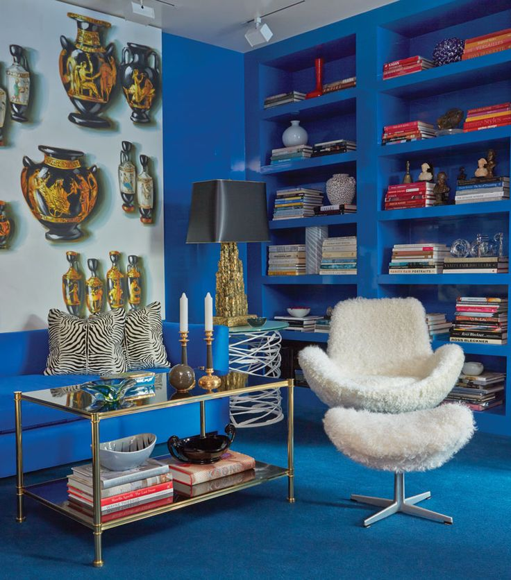 The cobalt blue library is vibrant, with textural and graphic accents in the curly lamb-covered vintage chair and ottoman, the side table by Paul Ferrante, and the zebra-striped pillows in Hermès silk.