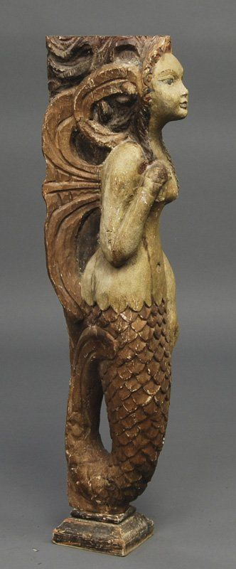 "Carved Folk Art Painted Mermaid Figure. The carved figure of a mermaid has curly hair and has one hand at her chest. Origin unknown. In good condition. Measures 32 1/2"" high, 6 1/4"" wide, 8 1/2"" deep."