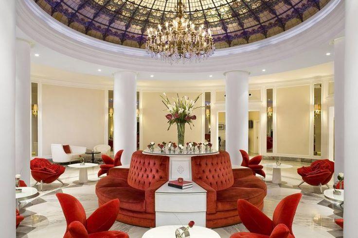 O lobby, predominantemente branco com sofás vermelhos sob uma majestosa cúpula de vidro, chama a atenção de quem entra no hotel.