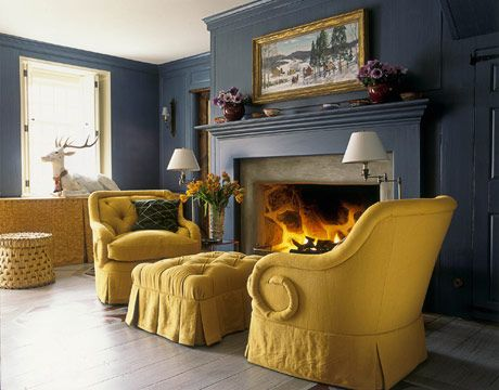 At the side of the entrance hall and golden as summer squash, a pair of inviting chairs — their arms curled into ram's horns — flank a blazing fire.