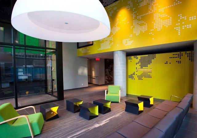 Entrée du projet de condo avec murs jaunes et plusieurs divans