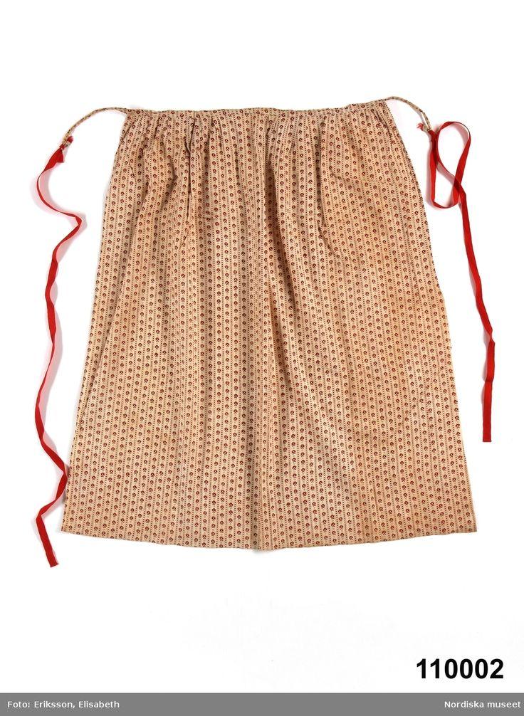 """Förkläde av  fin bomullslärft, vit botten med blocktryckt bårdmönster i rött, s.k. kattun.   Har i Ore använts till kyrkförkläde eftersom det var ett """"finare"""" köptyg. Ore, Dalarna, Sweden"""