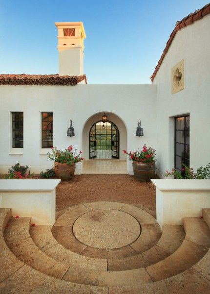 This courtyard reflects the Spanish style beautifully. Don't usually love this style, but the circular stairs and entry, the Moorish lanterns, and the bold bursts of color by the door. Lovely! Designed by Hugh Jefferson Randolph Architects of Austin, TX.