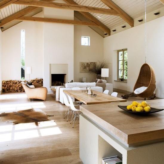 HYTTE. Høyt under taket, peis og åpen kjøkkenløsning i de duse fargene beige og hvit med noe stål.