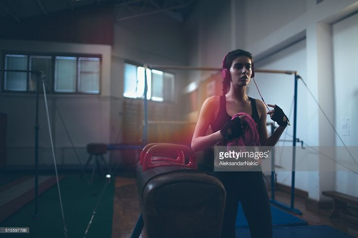 Photo of a young determined woman who is listening to the music during her intense workout