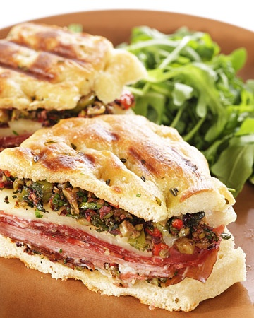Muffuletta Panini    A zesty topping of olives, anchovy, pickled peppers, and oregano tops Italian cold cuts in this interpretation of the famous New Orleans sandwich. This recipe is from Sean Rembold of Marlow and Sons restaurant in Brooklyn, New York.    Get the Muffuletta Panini Recipe