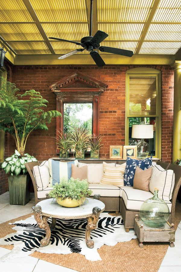 Durable accessories and furnishings give this porch a cozy living room feel. Patterned pillows and a faux zebra-skin rug are paired with natural colors and textures for a striking effect.  Key Elements of a Great Porch