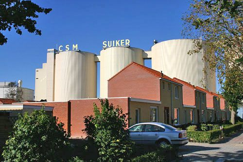 De suikerfabriek torent uit boven de huizen in het 'suikerdorp' Hoogkerk.<br>De CSM-fabriek is tegenwoordig eigendom van Cosun, het moederbedrijf van Suikerunie. De letters CSM zijn de afkorting van de 'Centrale Suiker Maatschappij' die in de jaren twintig van de vorige eeuw werd opgericht. De fabriek zelf stamt uit 1896.<br>De letters CSM zijn in september 2007 door Cosun van de silo's verwijderd. In 2008 nam de fabriek in Hoogkerk de naam 'Suikerunie' over van de fabriek in Groningen, die…