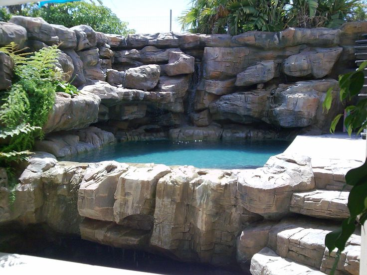 Elaborate rock pool with cascading waterfalls and privacy for Design of pond embankment