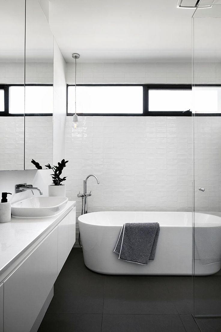 This modern and simple black and white bathroom has slightly textured white tiles, a standalone bathtub and a walk-in glass shower.