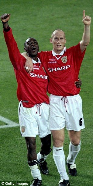 Stam and Andy Cole celebrate after winning the Champions League