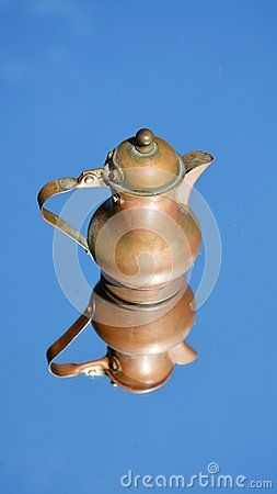 An  traditional small pitcher on a clean and blue background.