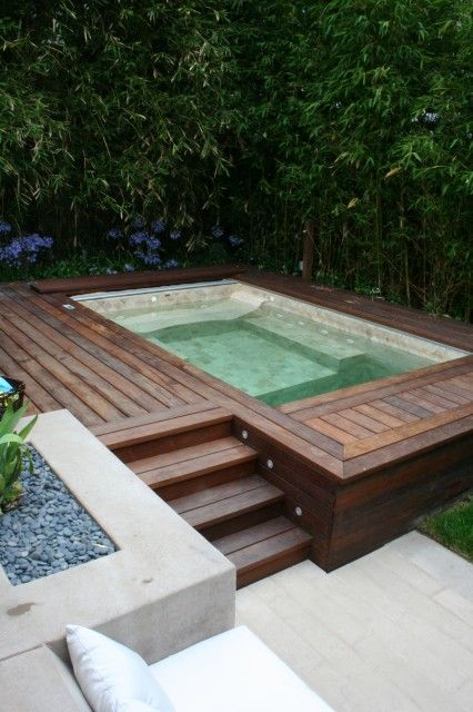 A true urban oasis… a hot tub nestles comfortably in a teakwood deck, flanked by a screen of bamboo, while a cushioned built-in stone seating area nearby provides further relaxation.