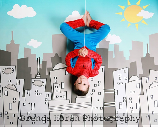 Superhero photo shoot! Paint some backdrops onto an old sheet, add props and photograph from ladder or stairs.