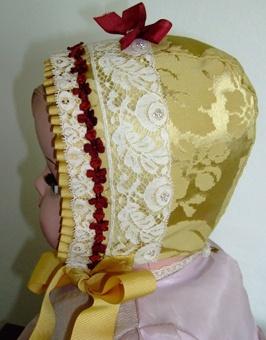 Dåpslue, gul med blomstrete bomullsfôr