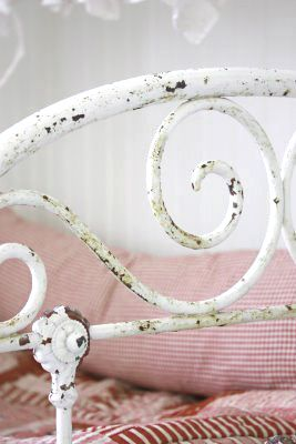 old wrought iron bed painted white, red bedlinens