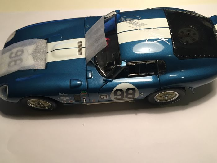 """Exoto - schaal 1/18/EG - Cobra Daytona Coupe #98 - ondertekend door Carroll Shelby  Ondertekend door CARROLL SHELBY ON THE ROOF'Limited Edition of 1965 pieces'VAN EXOTO-WEBSITE:Tien jaar na een Shelby Amerikaanse """"garage sale"""" hebben gehouden begon Carroll Shelby de zoektocht naar een Cobra Daytona Coupe dat hij kon kopen. CSX2300 de """"Ford van Frankrijk Coupe"""" een auto die was verkocht in de """"garage sale"""" bevond zich in Japan gekocht en keerde terug naar Shelby. De auto ging in opslag voor…"""
