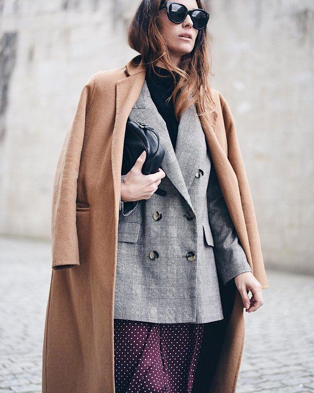 Te proponemos un look que combina un jersey negro de cuello alto con un abrigo gris a cuadros. Lo interesante viene cuando a estas piezas lñe sumamos una falda púrpura con estampado de bolas y un abrigo largo en color café claro.