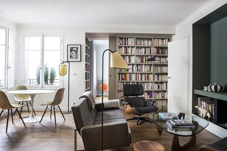 Small Paris apartment living room with Saarinen dining table and built-in shelves, designed by architect Philippe Harden