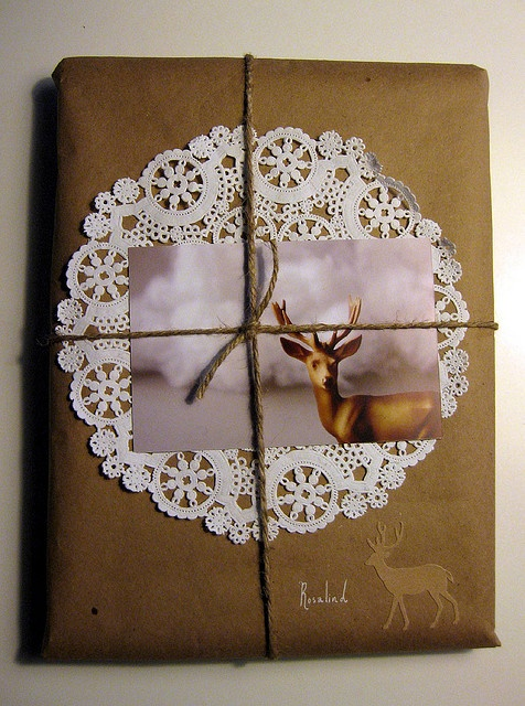 Brown paper wrapping with paper doily, twine, and deer picture.