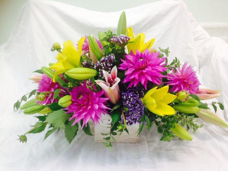 Summer delight. Fresh bright yellow lilies and bright pink dahlias with a touch of purple statice. For any occasion