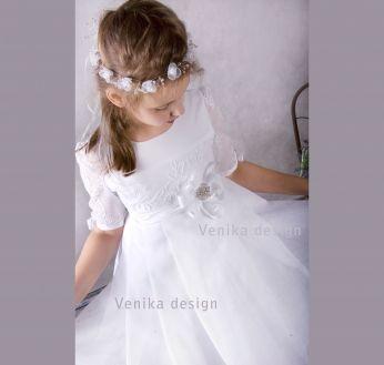 Wyjątkowo delikatna sukienka komunijna z piękną broszką i kwiatem w pasie