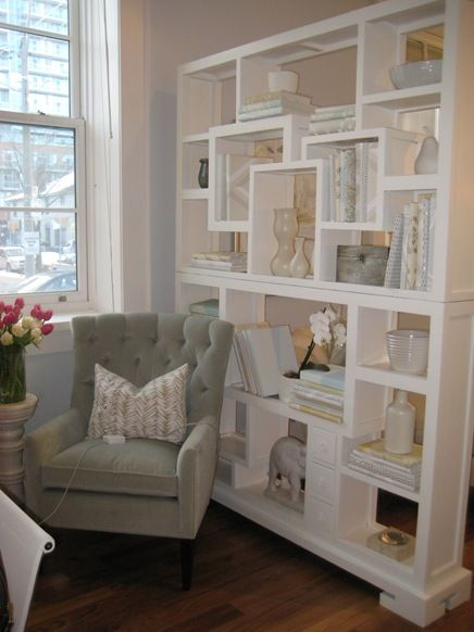 Room dividers - White bookshelf used s a room divider. This helps to define spaces.