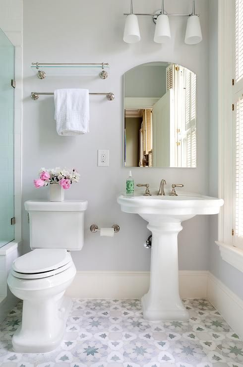 Beautiful white and gray bathroom is equipped with a 3 downlight linear sconce mounted to a light gray wall above an arched vanity mirror fixed above a white pedestal sink placed on gray and blue mosaic floor tiles beside a toilet.