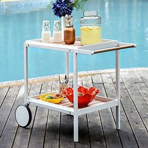 Send the party outside with this handy serving cart! The sleek white finish offers a modern framework and slatted panels line the two shelf tiers. #JMDFurniture #Modern #Outdoors