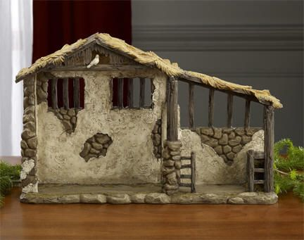 """First Christmas Gifts Lighted Stable to match the #16609 7"""" Nativity Figures or any other 6"""" or 7"""" nativity figures   The stable is designed to capture the reality of the humble stable where Jesus was born. The stable depicts stone and stucco walls, weathered log beams and posts and a humble, palm thatched roof. Included in the stable is a light that shines down on the manger below. Measures: 15"""" wide x 9 5/8"""" high x 4 1/4"""" deep. Polymer resin. Batteries included. (Item #16620) $64.95"""