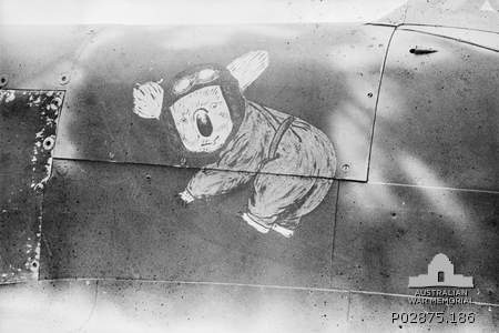 Kiriwina, Trobriand Islands, Papua. September 1943. Nose art, a drawing of a koala dressed as a pilot, on the port side engine cowlings covering the main fuel tanks immediately in front of the pilot's cockpit of a No. 79 Squadron RAAF Spitfire Mk Vc aircraft.