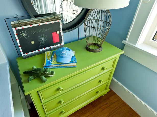 A country-style dresser, fashioned from maple and other American hardwoods, turns focal point when presented in a vivid shade of apple green. An open cage lamp and chalkboard art add a whimsical touch on the dresser top.