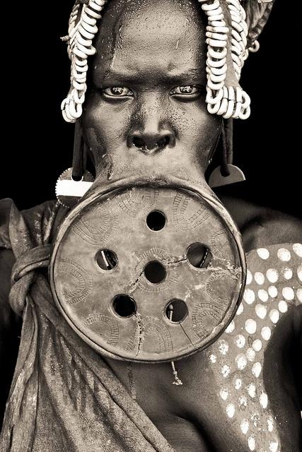Entre los Surma ( propio nombre Suri ) y Mursi gente del valle inferior del río Omo, en Etiopía , a unos 6 a 12 meses antes del matrimonio de labios de la mujer es perforado por su madre o una de sus parientas , por lo general en torno a la edad de 15 a 18 . la perforación inicial se realiza como una incisión del labio inferior de 1 a 2 cm de longitud , y se inserta una clavija de madera sencilla .