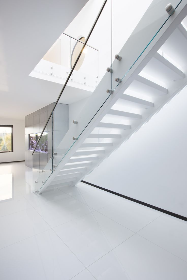 Very puristic interior with a minimal design staircase concept. Wood stringer staircase with white strings and treads combined with glass railing. Not from this world www.stairs-siller.com/modern-stairs/
