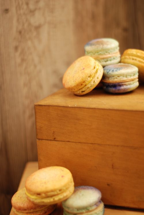 Handpainted Saffron-Orange Blossom macarons on Orange-Pistachio shells and Moroccan Spiced Coffee macarons on vintage wooden boxes.