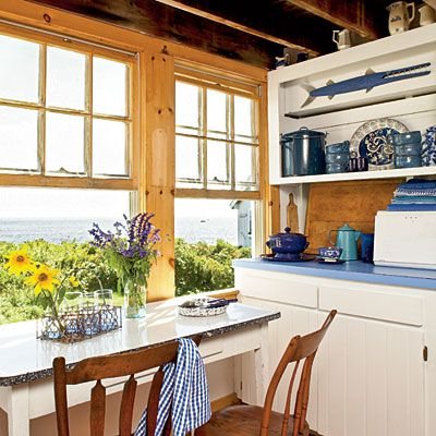 Kitchen with a View: The small breakfast table placed square in front of the windows provides the best view of the waves crashing off Casco Bay. A collection of enamelware in the kitchen's open cabinets came with the house and was—surprisingly—in the homeowner's favorite shades of blue.