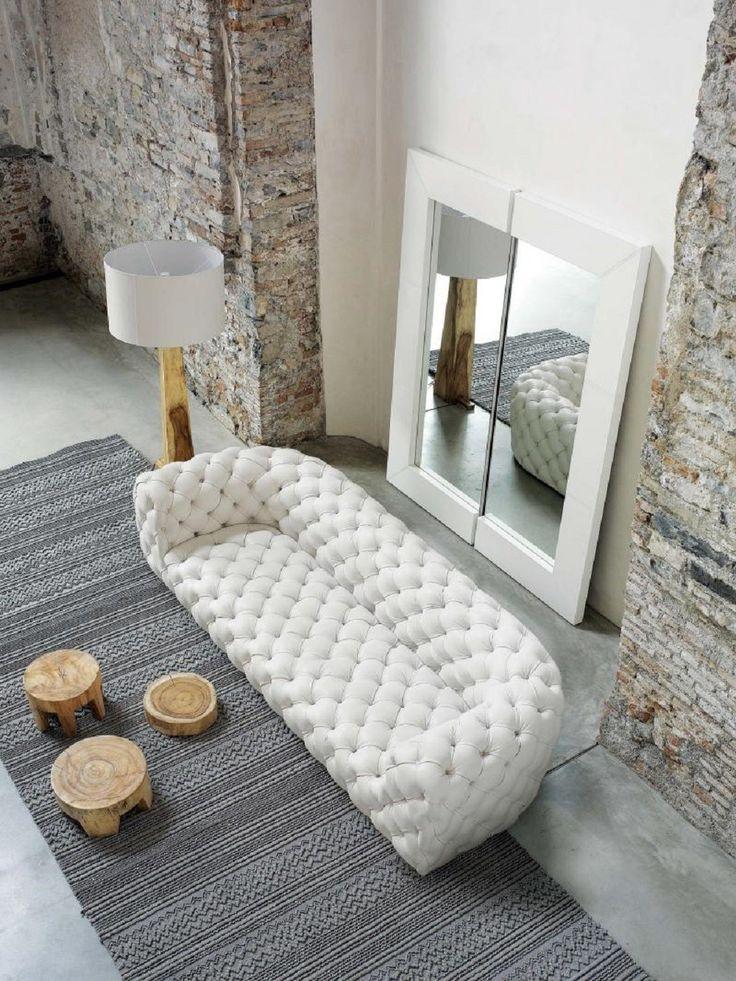 Biała pikowana sofa w salonie z kamienną ścianą