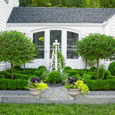 Dwarf lilac standards and boxwood flank a tuteur trellis threaded with clematis and morning glories in this formal garden that fronts a breezeway connecting kitchen to garage. | Photo: Tria Giovanthisoldhouse.com | from A DIYer's Delight in a Colonial Revival Remodel