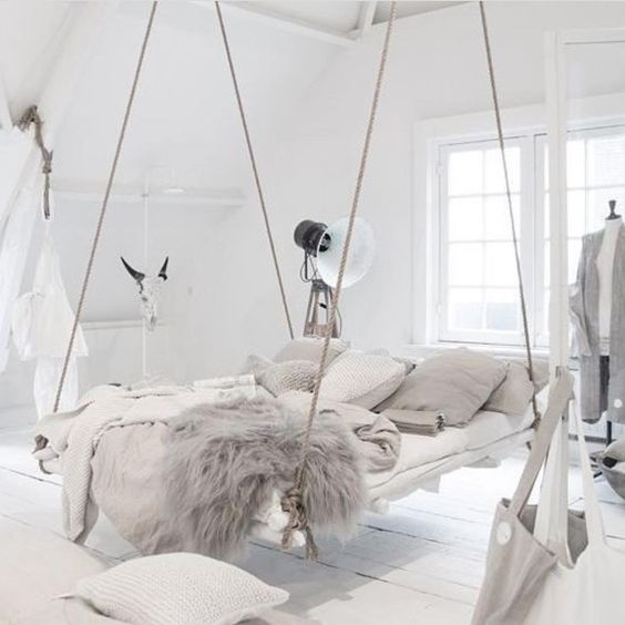 Boho rustic bedroom with a bed hung by ropes