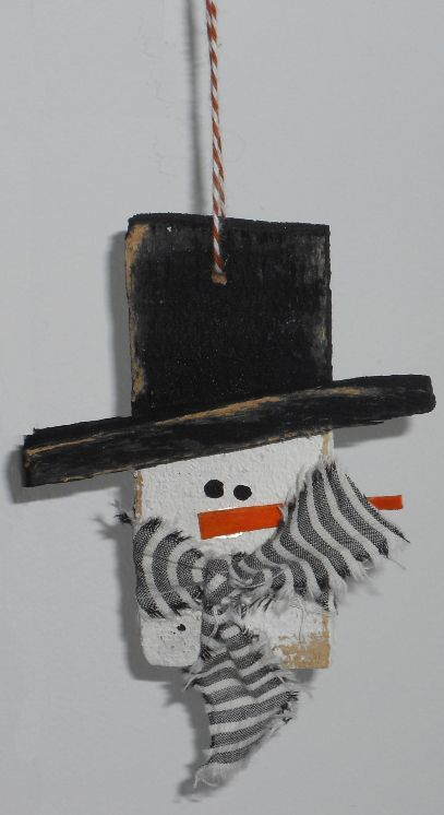 "We used old slats from a friend's renovation project. ruff cut wood, measures 1 1/2"" X 1/2""  X about 4"" long.  Use a scrap piece of wood for the hat brim, glue on and paint the hat black and the face white. Ruff the edges up a little and the nose is another scrap piece of wood painted orange. Add the eyes and scarf. Drill a hole to hang him with."